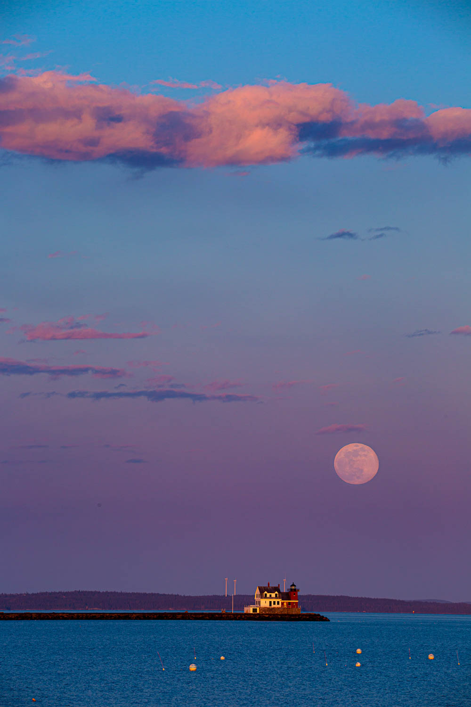 Full moon rises over Rockland Breakwater Lighthouse.